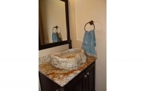 Lakehouse rental half bath with hollowed-out rock sink